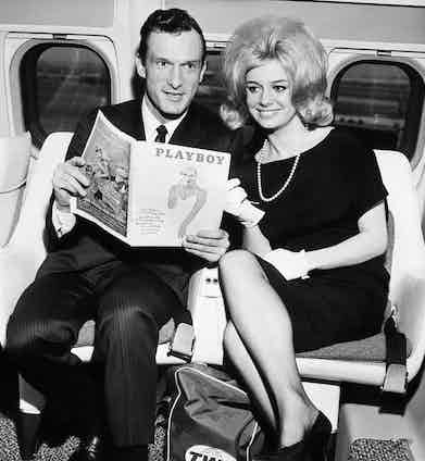 The Editor and Publisher of Playboy with Cynthia Maddox, the cover girl on the February issue of his magazine in 1962, arriving by TWA superjet from Chicago. They are to attend a party given by Ella Fitzgerald at the Basin Street East in honour of winners of the Playboys jazz poll.