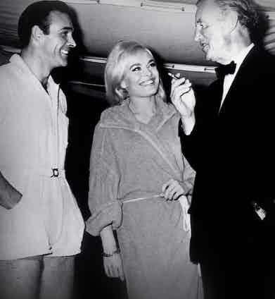 On the set of Goldfinger Fleming entertains Sean Connery and Bond girl Shirley Eaton in 1964. Goldfinger has been the most highly praised Bond picture of all time. It was after Goldfinger that Bond became a true phenomenon.