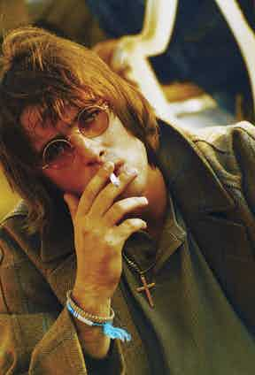 Gallagher channels John Lennon with round glasses and a cigarette in Finsbury Park, 1996. Photo by Jadranka Krsteska/Redferns.