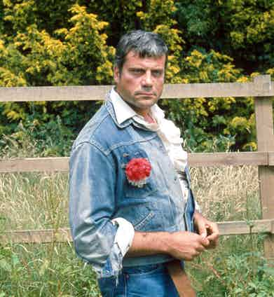 Wearing a double denim ensemble over a white ruffled poet shirt and finished with a red carnation, 1980. Photo by Mike Kenny/REX/Shutterstock.
