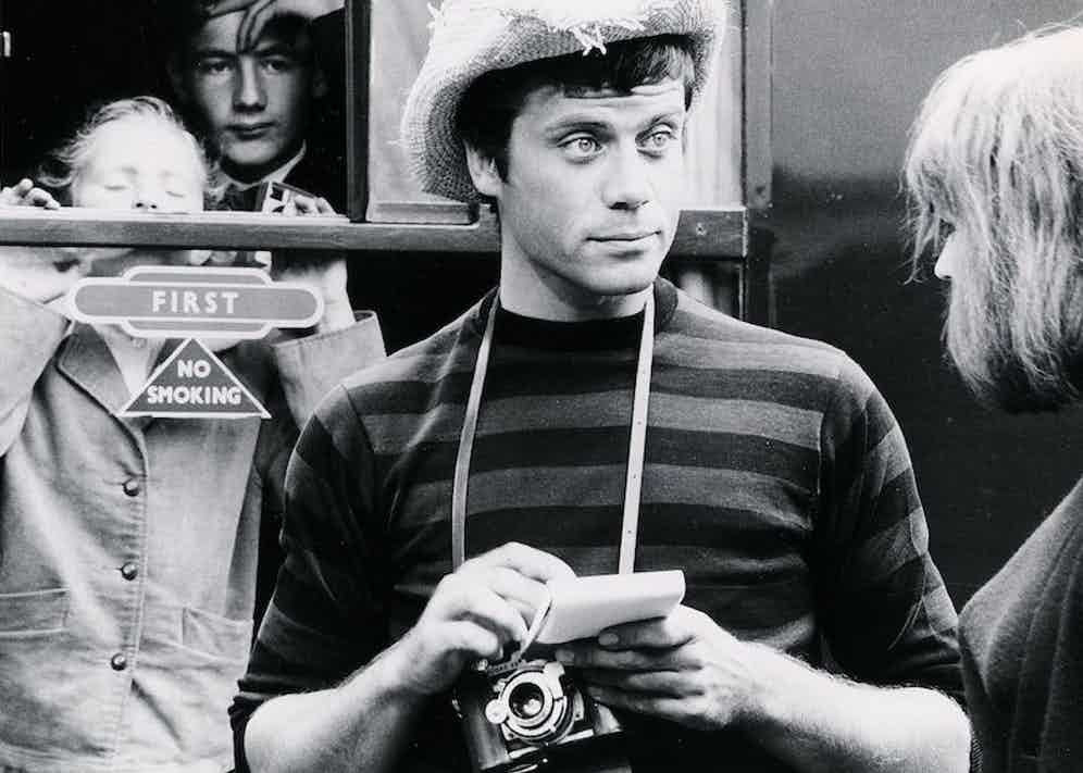 Reed wears a straw cowboy hat, striped sweater and carries a classic manual film camera as Tinker the tourist photographer in British drama The System, 1964. Photograph by British Lion/Bryanston/Kobal/REX/Shutterstock.