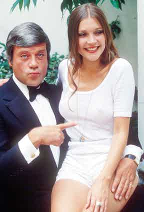 In a black dinner jacket, white dress shirt, bow tie and gold cufflinks with Judy Buxton after the filming of Michael Winner's remake of The Big Sleep, 1977. Photograph by Chris Capstick/REX/Shutterstock.
