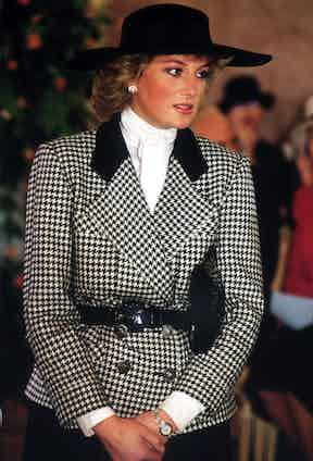 In 1987 on a German tour, Diana wears a conservative houndstooth jacket with black collar designed byAlistair Blair, with a hat by milliner Philip Somerville, and her signature pearl earrings.