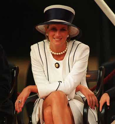 In a white two-piece with an elegant black trim, oversized pearls, and matching millinery at VJ Day celebrations, 1995. On her left hand is the engagement ring given to her by Prince Charles, made by Garrard & Co.