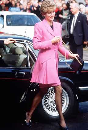 Wearing a hot pink frock coat made by Catherine Walker and carrying a Salvatore Ferragamo bag, 1991.