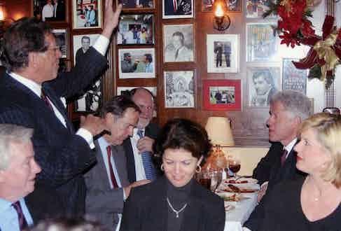 President Bill Clinton breaks bread with Thomas Kean and Jon Corzine as Frank Pellegrino Sr. (standing) regales them, 2003. By Nancy Ellison/Polaris Images.