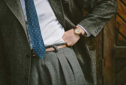London-born tailor James Turner wears a grey wool and cashmere blend jacket with three buttons on the sleeve over a classic Oxford shirt with pleated cuffs. He has turned the shirt sleeves back once as an intentional sartorial twist and paired the ensemble with a vintage rose gold watch with a brown leather strap. Photograph by Jamie Ferguson.