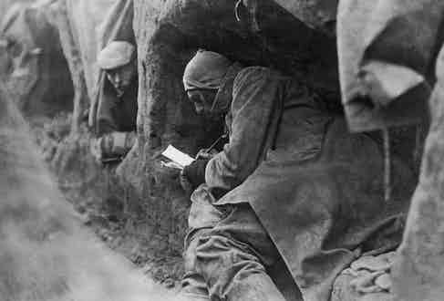 A British soldier savours a chance to write home whilst sheltering in a trench.