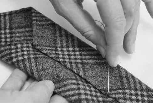 Hand-stitching Fumagalli's ties together.