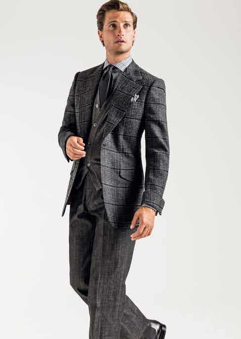 Charcoal urban tweed hacking jacket, flannel grey sleeveless cashmere cardigan, black Prince of Wales check spread collar shirt, black shantung grenadine silk tie, New York print pocket square and pleated black denim trousers, all Huntsman for The Rake; black leather Chelsea boots, Carmina for The Rake. Photo by James Munro.