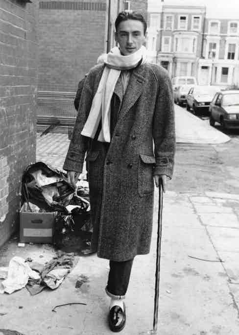 Arriving to record the Band Aid record Do They Know It's Christmas in 1984. Weller wears an oversized herringbone tweed double-breasted coat, a scarf nonchalantly draped over one shoulder, selvedge denim jeans, and white socks with tassel loafers. Note also the rakish addition of a wooden cane.