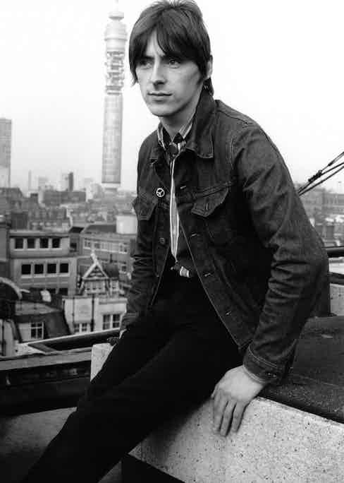 Demonstrating his style versatility, wearing a denim trucker jacket, striped shirt and slim trousers in London, 1982. (Photo by Erica Echenberg/Redferns).