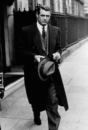 Cary Grant rocking a three-piece beneath a heavy wool overcoat, circa 1950s.