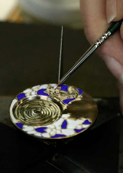 Painting white enamel details onto a gold and blue enamel design.