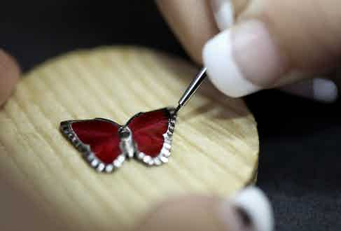 A butterfly is hand-enamelled.