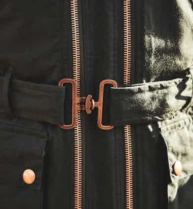 Hand-crafted in Manchester, this piece is made from waxed cotton and features four utilitarian front patch pockets, a collar fastening, and fully adjustable surcingle clip belted waist.