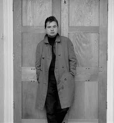 British painter Francis Bacon wears a double-breasted raincoat in London, circa 1963. Photograph by John Deakin.