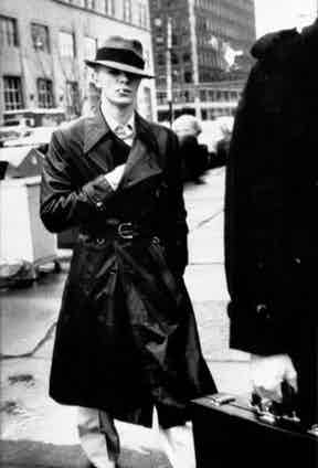 David Bowie wears a double-breasted trench coat with a belted waist, circa 1976.