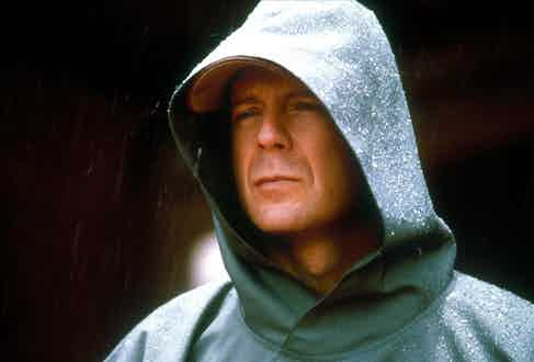 Bruce Willis demonstrates a hooded raincoat in Unbreakable, 2000. Photograph by AF archive/AlamyStock Photo.