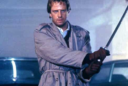 Christopher Lambert wears a grey trench coat with a belted waist and epaulettes in Highlander, 1986. Photograph by Moviestore/REX/Shutterstock.