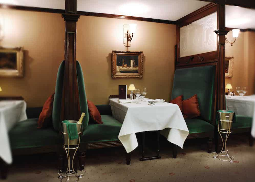 Sumptuous green velvet lines the seats of Wiltons' booths, framed in dark mahogany with renaissance artworks on the walls.