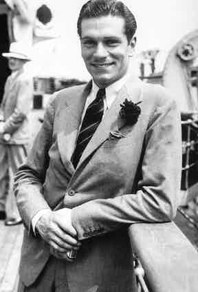 Sir Laurence Olivier in a single-breasted flannel suit with a rakish boutonniere, 1933.