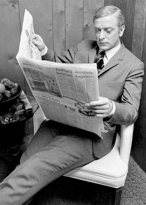 Michael Caine reading a newspaper in the 1960s, wearing a sombre grey suit.