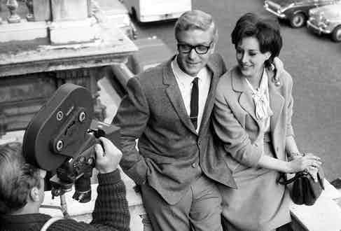Michael Caine with his arm around the beautiful Sue Lloyd during the filming of The Ipcress File, circa 1965.