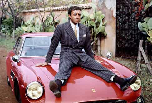 Peter Sellers in a double-breasted pinstriped suit looking very much at home atop his 1965 Ferrari 500 Superfast.