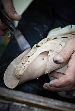 Leather sections of a shoe being moulded around a last.