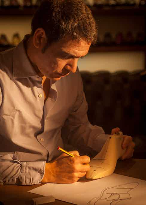 Paolo Scafora marking a wooden last with pencil.
