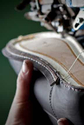 The sole of a shoe being sewn in the workroom.