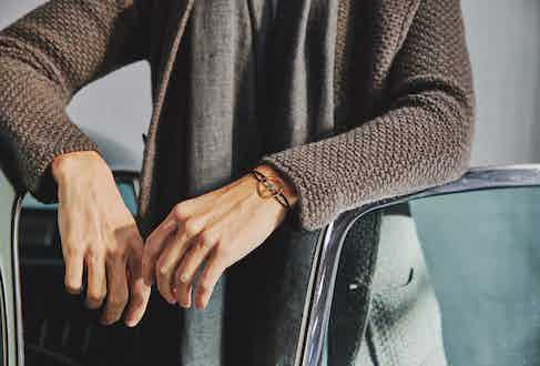 Chocolate single-breasted merino and cashmere jacket and silver birdseye weave cashmere scarf, both Anderson & Sheppard; gold steering wheel bracelet on black cord, The Mechanists.