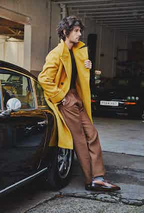 Mustard wool Casentino ulster coat, Rubinacci; Brown cashmere tobacco pleated front linen trousers, Huntsman; Chocolate crew neck cashmere sweater, Anderson & Sheppard; Grey merino wool socks, Pantherella; Brown Andy Démesure leather loafer, Berluti.