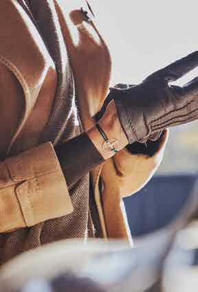 Camel double-breasted overcoat Lardini; Chocolate crew neck cashmere sweater and brown cashmere and wool scarf both Anderson & Sheppard; Black E8 super slim tapered selvedge denim jean, Blackhorse Lane; Racing green gold steering wheel on British green cord,The Mechanists; Brown cashmere lined lambskin gloves, Omega SRL.