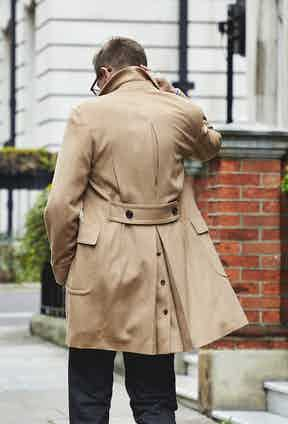 Lardini's double-breasted camel overcoat features an inverted box pleated back, half-belt and patch pockets.
