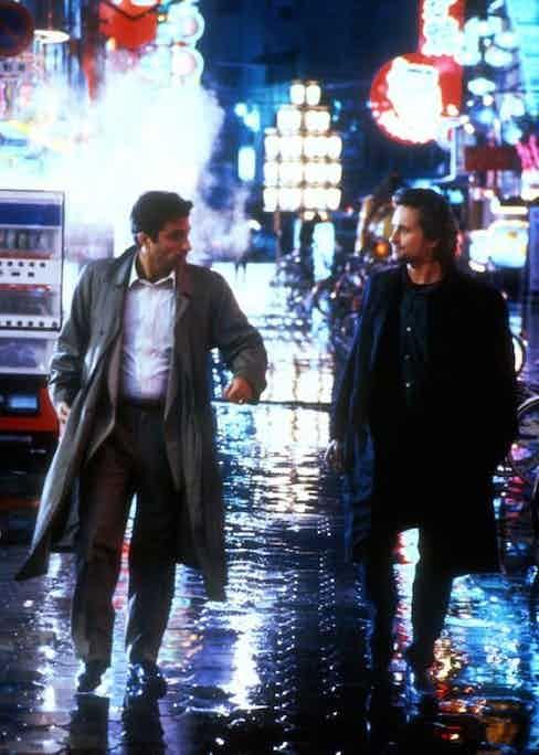 Andy Garcia and Michael Douglas wearing raincoats in Black Rain, 1989.
