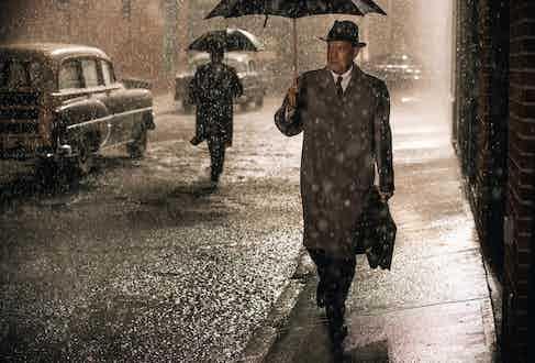 Tom Hanks wearing a mackintosh-style raincoat in Bridge of Spies, 2015.