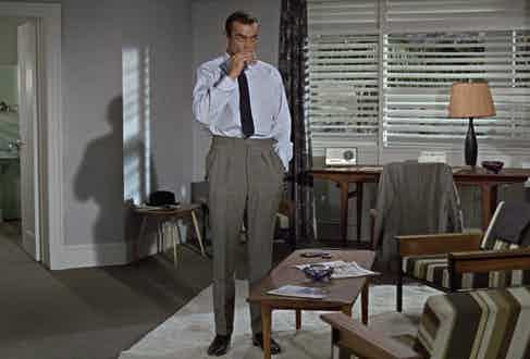 Sean Connery's James Bond shows another way to wear wide trousers in Dr No, 1960. Although high-waisted and with twin pleats, the trousers taper gently down to a narrow opening, giving them more of a contemporary feel even today.