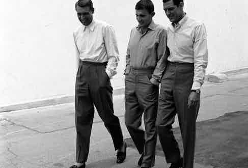 Famous for his elegant, full-cut suits, Cary Grant here shuns the tie, and wears his wide-legged, twin pleaters with a white shirt and tassel loafers, circa 1950s.