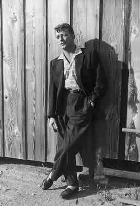 Robert Mitchum wears wide-legged trousers and a full cut jacket, with a cuban-collar shirt underneath, circa 1940s.