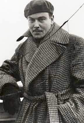 Nils Asther wearing an oversized trench-style coat in a houndstooth wool, complete with large lapels and a belted waist, 1935.