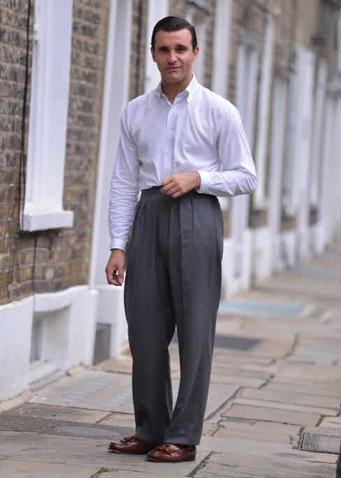 James Turner wears pleated, wide-legged trousers by Scott Fraser with a white Oxford shirt and G.H Bass tassel loafers. His ensemble harks back to Hollywood's 'Golden Age', showcasing how the look is just as elegant today as it was sixty years ago.
