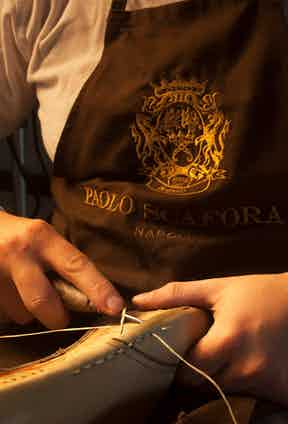 The welt being prepared and stitched by a craftsman.