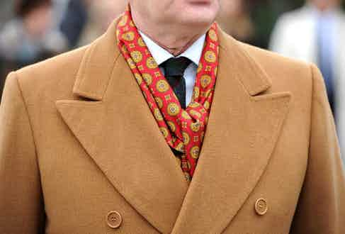 A camel overcoat is paired with a complementary patterned silk scarf for more formal occasions. Photograph by Gentleman's Gazette.