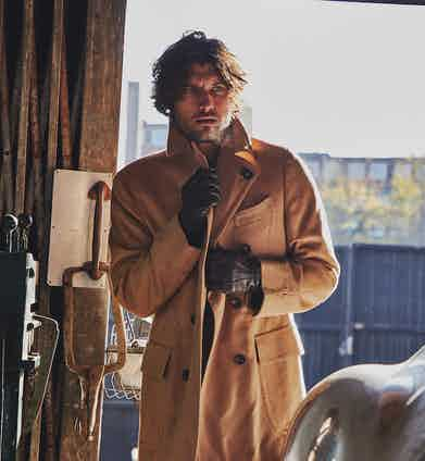 This camel double-breasted overcoat by Lardini pairs perfectly with smart winter gloves such as these brown cashmere lined lambskin ones by Omega SRL. Photograph by James Munro.