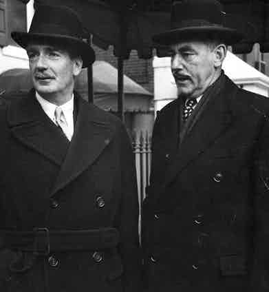 British Foreign Secretary Anthony Eden wears a double-breasted belted overcoat and bowler hat accompanied by the American Secretary of State, Dean Acheson in London, 1952.