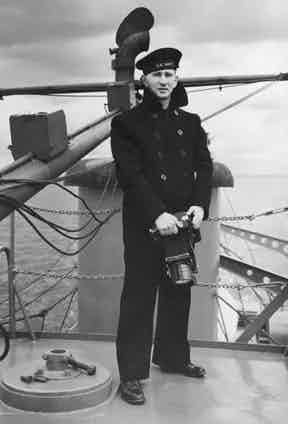 American Naval photographer Morris Engel wears a traditional double-breasted reefer jacket on the deck of a ship, circa 1945.