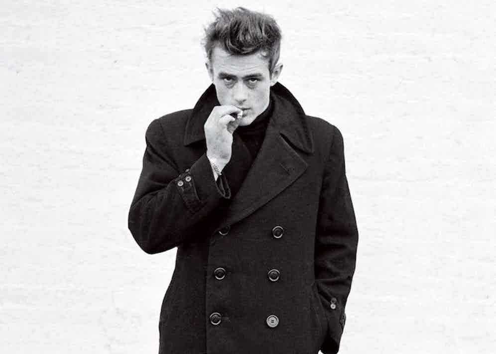 James Dean's overcoat features an eight-button double-breasted closure and adjustable cuffs, worn with a popped collar in New York, 1955. Photograph by Dennis Stock.
