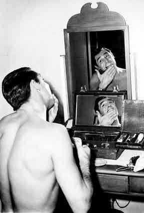 Cary Grant applies aftershave on a break during the filming of Arsenic and Old Lace, 1941.